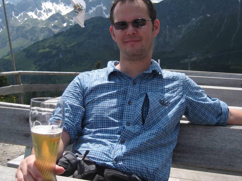 Einkehr auf dem Weg zum Gipfel vor einer Hütte mit einem Radler
