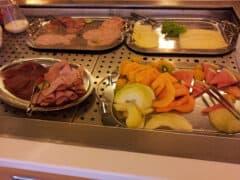 Blick auf Wurst, Käse, Melonen bei einem gerade etwas leer geräuberten Frühstücksbuffett