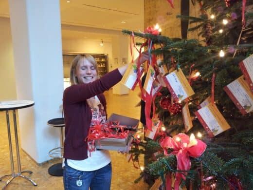 Bild von jana Stähle vom Kinderbüro Stuttgart, wie sie neue Karten mit Kinderwünschen an den Kinderwunschbaum hängt
