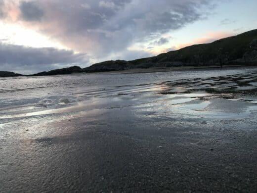 Sonnenreste spiegeln sich im Wasser am Strand von Glencolmcille