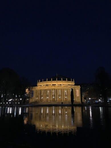 Das Stuttgarter Opernhaus in der Nacht mit Spiegelung im Eckensee