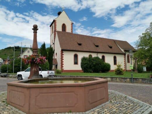 Nicht bezeichneter Brunnen auf dem Brunnenpfad mit Kirche