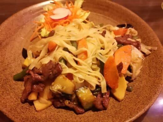 Pho Xao Bo Cay (Gebratene Reisbandnudeln mit Rindfleisch, Zitronengras, Knoblauch, Karotten, Bambus, Stangenbohnen, Chinakohl und Zwiebeln) im Ha Long