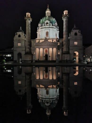 Die Karlskirche Wien spiegelt sich wunderbar bei Nacht im Wasser davor