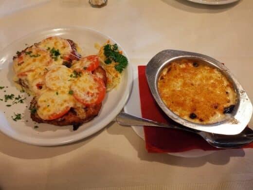 """Schnitzel »Schweizer Art«, mit Tomaten und Käse überbacken mit """"Sahnekartoffeln"""" (Kartoffelgratin) im Max Walloschke Hannover"""