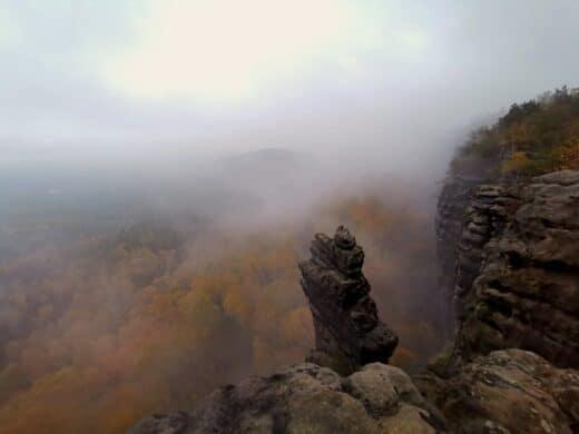 Nebel wabert durch die Felsen und den herbstlichen Wald am Gohrisch