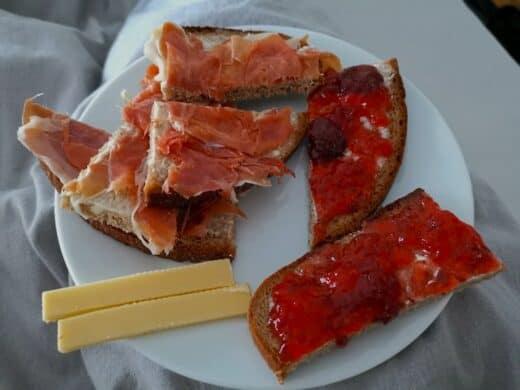 Gemütliches Frühstücken im Bett mit Schinken, Marmelade und Käse