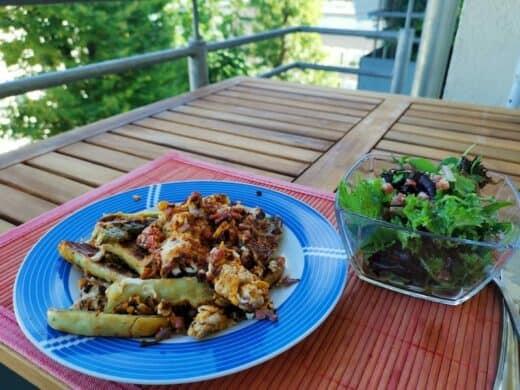 Maultaschen gebraten mit Ei und Speck sowie Salat auf dem Balkon