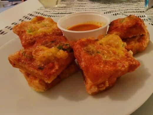 frittiertes Brot mit gehacktem Hühnchenfleisch, Erdnussoße und Gurkensoße