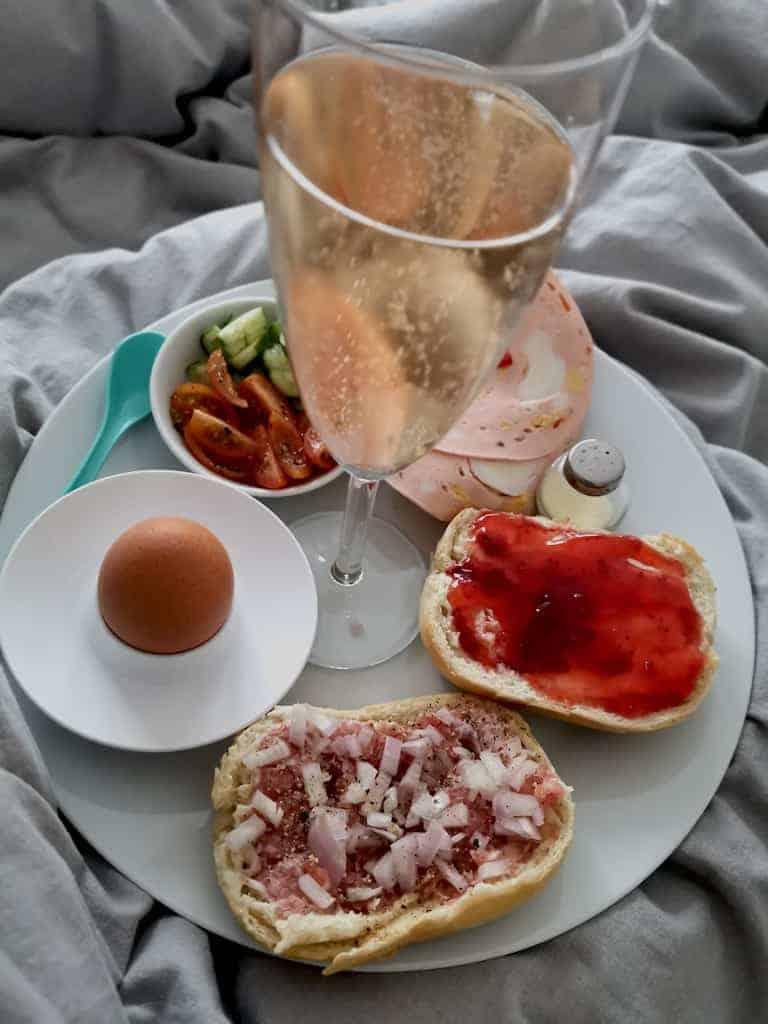 Spätstück im Bett mit Sekt, Ei und Brötchen mit Mett, Lyoner und Marmelade