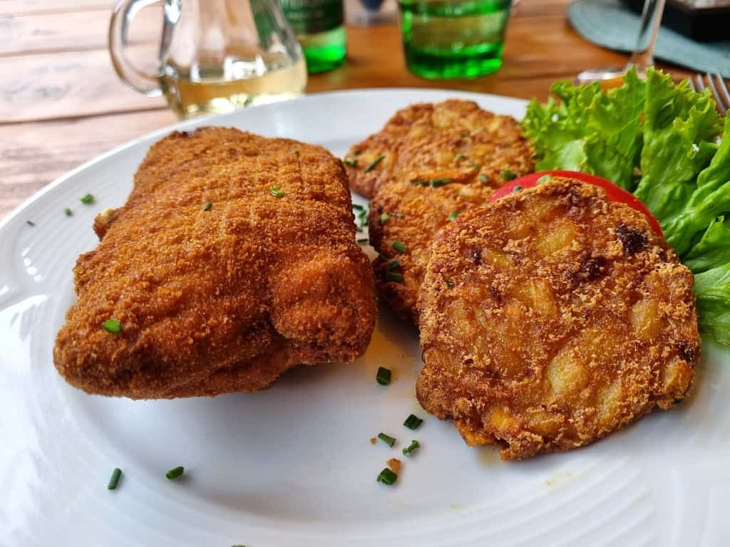 Holzfällerschnitzel (gefüllt mit Dijonsenf, Speck, Essiggurken, Zwiebeln und Bergkäse), dazu Speckrösti und Krautsalat im Cafe Leitner Ehrwald)
