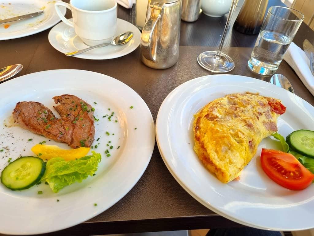 Omelette mit Schinken, Speck, Tomate und Käse mit Steak zum Frühstück im Radisson Blu Altstadt Hotel Salzburg
