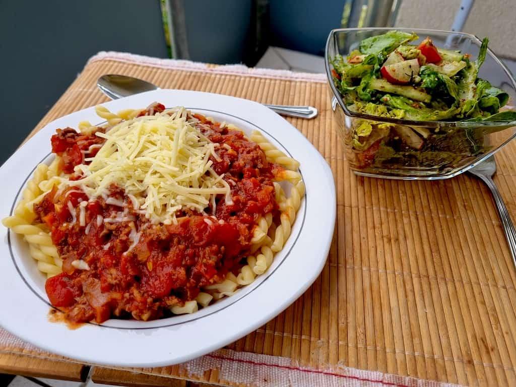 Fertige Bolognese mit Salat auf dem Balkon