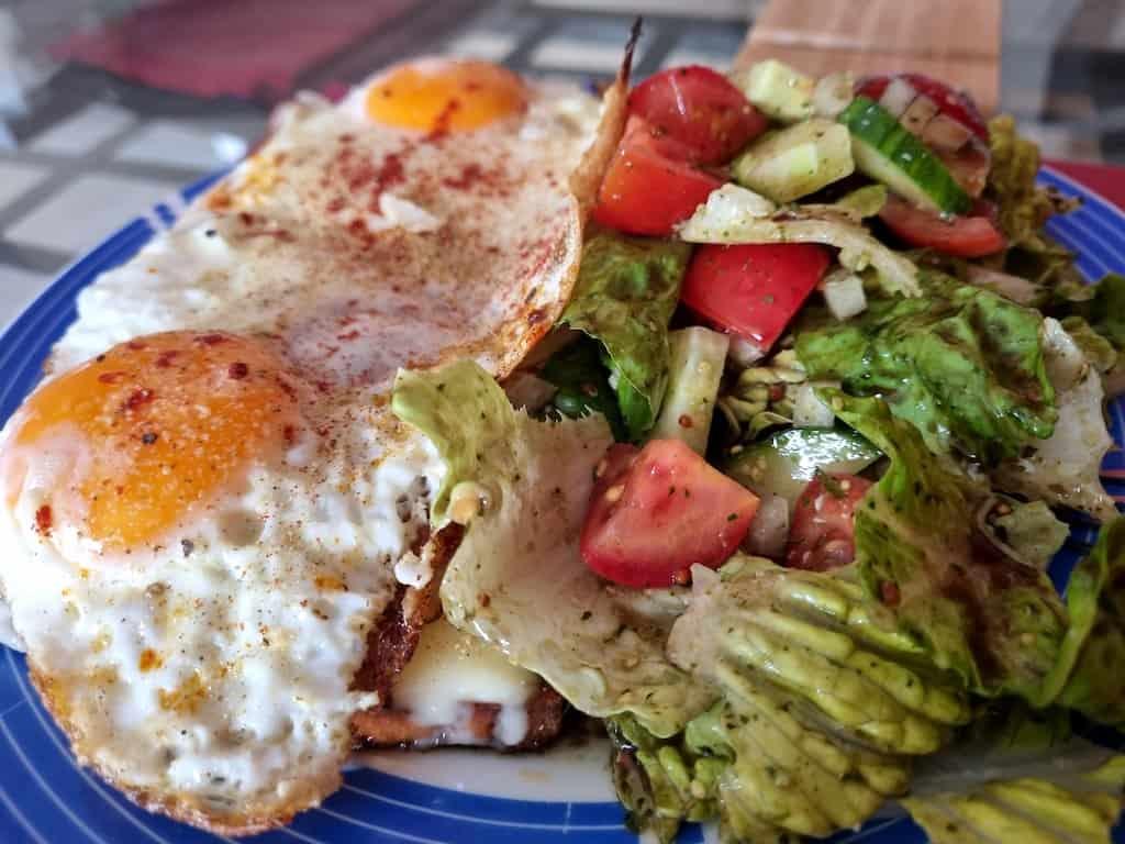 Fleischkäse mit Käse, Zwiebeln und Spiegeleiern mit Salat