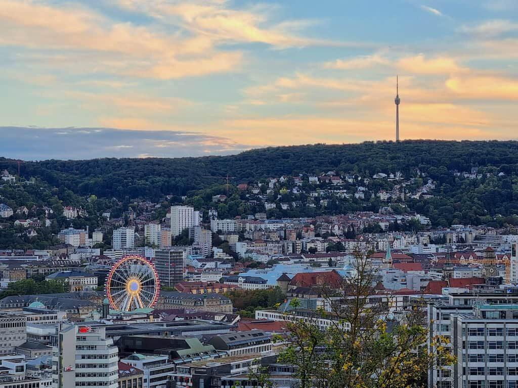 Blick in den Sonnenuntergang über Stuttgart - mit Riesenrad vor dem neuen Schloss und Fernsehturm
